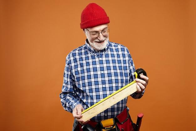 Poziome Ujęcie Przedstawiające Pozytywnie Wykwalifikowanego Starszego Europejskiego Rzemieślnika, Noszącego Perły I Okulary, Trzymającego Przyszłe Drewniane Meble, Mierzącego Jego Rozmiar I Uśmiechniętego, Cieszącego Się Pracą Ręczną Darmowe Zdjęcia