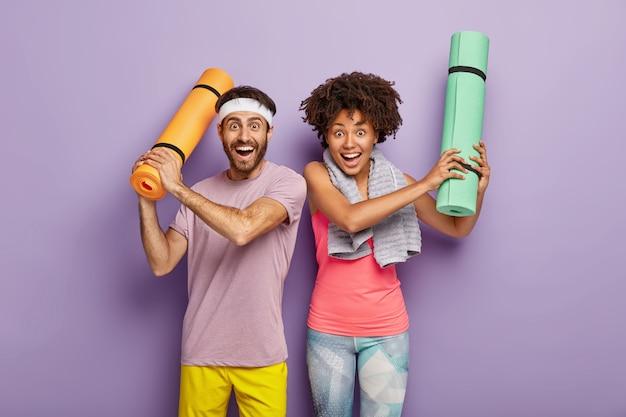 Poziome Ujęcie Szczęśliwej Kobiety I Mężczyzny Bawią Się Po Aerobiku, Podnoszą Ręce Ze Złożonymi Karematami, Ubrani W Odzież Sportową, Cieszą Się Wolnym Czasem Na Sport, Odizolowane Na Fioletowej ścianie. Zróżnicowana Para Darmowe Zdjęcia