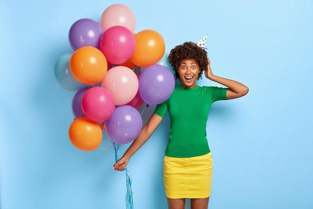 Poziome Ujęcie Uradowanej Kobiety Trzymającej Wielobarwne Balony Pozując Z Urodzinowym Kapeluszem Darmowe Zdjęcia