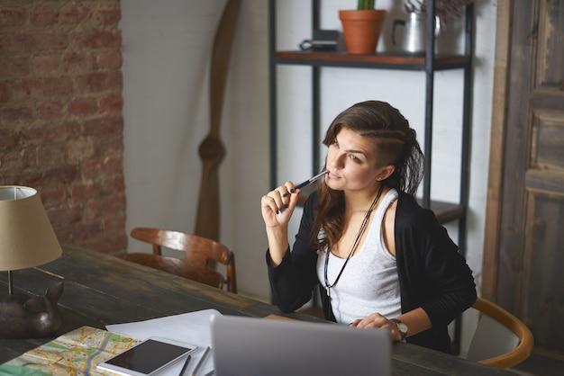 Poziome Ujęcie Wewnętrzne Pięknej Młodej Kobiety Ze Stylową Fryzurą Pracującej W Domowym Biurze, Siedzącej Przed Typowym Laptopem, O Zamyślonym Wyglądzie, Marzącej O Wakacjach Nad Morzem Darmowe Zdjęcia