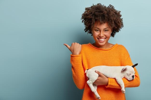 Poziome Ujęcie Zadowolonej Kobiety Afro Wskazuje Na Wolne Miejsce, Wskazuje Kierunek Do Sklepu Zoologicznego, Kupił Szczeniaka Rodowodowego, Ma Przyjemny Uśmiech Na Twarzach Modelek Na Niebieskiej ścianie. Miłość Między Psem A Właścicielem Darmowe Zdjęcia