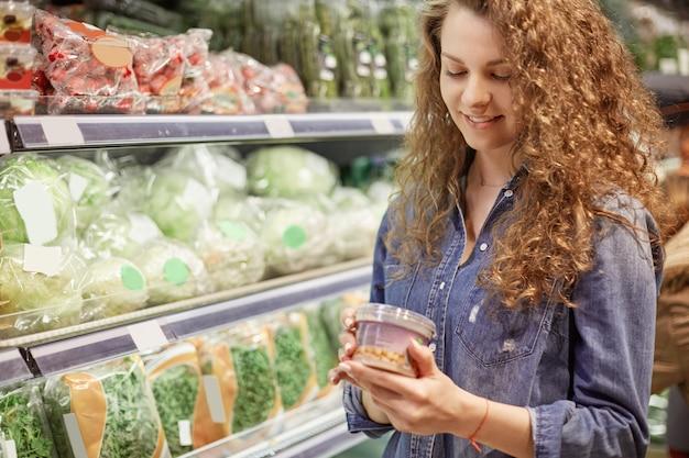 Poziome Ujęcie Zadowolonej Kobiety Kupuje Jedzenie W Supermarkecie, Czyta Informacje O Produkcie, Wybiera Niezbędny Produkt Do Przygotowania Kolacji, Będąc W Dziale Warzywnym. Koncepcja Ludzie I Zakupy Premium Zdjęcia