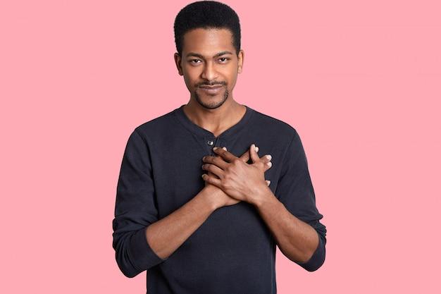 Poziomo Pod Wrażeniem Dotknięty Mężczyzna Trzyma Ręce Na Piersi, Wyraża Wdzięczność, Słyszy Przeszywające Słowa, Ubrany W Swobodny Sweter, Na Różowo. Ludzie I Wdzięczność Premium Zdjęcia