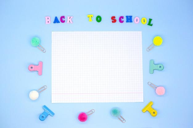 Poziomy Notatnik Na Niebieskim Tle Otoczony Spinaczami I Segregatorami Obok Napisu - Powrót Do Szkoły Premium Zdjęcia