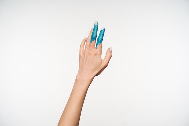 Poziomy Portret Dłoni ładnej Młodej Damy Malowanej Na Niebiesko, Podnosząc Ją Do Góry, Pozując Na Biało. Koncepcja Języka Ciała Darmowe Zdjęcia