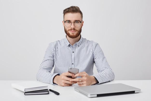 Poziomy Portret Nieogolony, Przyjemnie Wyglądający Młody Biznesmen Siedzi Przy Biurku Darmowe Zdjęcia