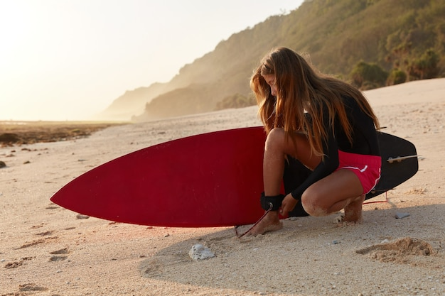 Poziomy Widok Profesjonalnego Surfera Zapina Smycz Pod Kątem, Zapewniając Bezpieczną Walkę Z Falami Darmowe Zdjęcia