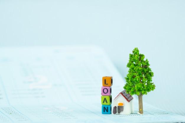 Pożyczka tekst i mały model domu i drzewko z notatnikiem Premium Zdjęcia