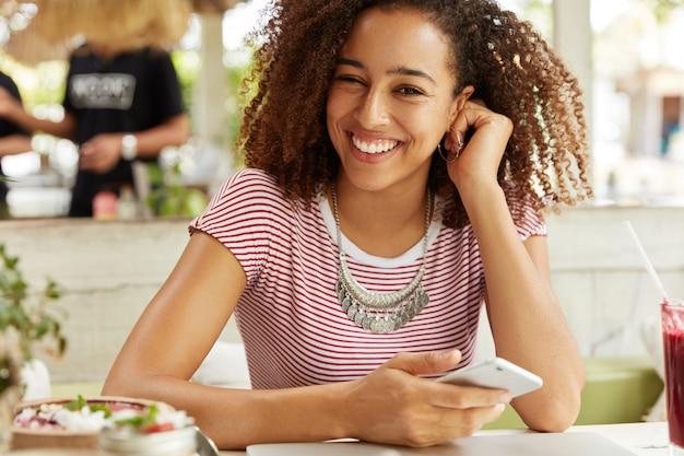 Pozytywna Afroamerykanka O Wesołym Wyglądzie, Chętnie Rozmawiająca Ze Znajomymi, Korzysta Z Nowoczesnego Telefonu Komórkowego, Siedzi W Stołówce, Je Pyszne Desery I Pije Koktajl. Technologia, Koncepcja Odpoczynku Darmowe Zdjęcia