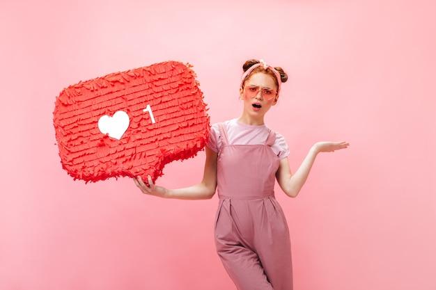 Pozytywna Dama Ubrana W Różowy Kombinezon, T-shirt I Różowe Dodatki Wskazuje Palcem Na Podobny Znak. Darmowe Zdjęcia