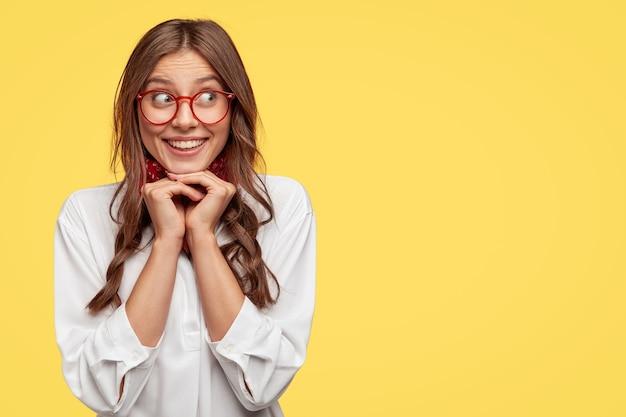 Pozytywna Kaukaska Kobieta Z Delikatnym Uśmiechem, Trzyma Ręce Pod Brodą, Pozytywnie Chichocze Na Bok, Ubrana W Białą Koszulę, Stoi Pod żółtą ścianą Z Wolną Przestrzenią Na Twoje Materiały Promocyjne Darmowe Zdjęcia