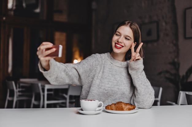 Pozytywna Krótkowłosa Dziewczyna Z Czerwoną Szminką I śnieżnobiałym Uśmiechem Robi Selfie W Kawiarni I Pokazuje Znak Pokoju. Darmowe Zdjęcia