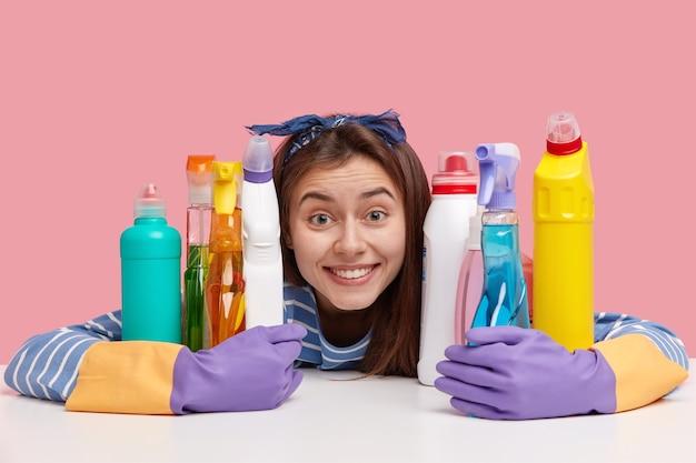 Pozytywna Młoda Kobieta O Zachwyconym Wyrazie, Zębowatym Uśmiechu, Wchłaniająca Chemiczne Detergenty, Wygląda Radośnie Darmowe Zdjęcia