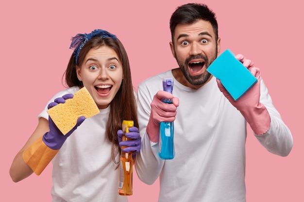 Pozytywna Młoda Para Rodzinna Ma Pozytywny Wyraz Twarzy, Używa Chemicznego Sprayu Do Mycia I Gąbki Do Mycia Okien W Pokoju Darmowe Zdjęcia