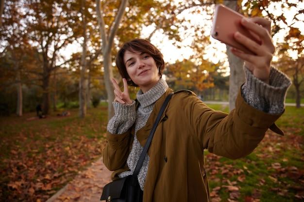 Pozytywna Młoda Piękna Krótkowłosa Brunetka Kobieta Podnosząca Rękę Ze Znakiem Pokoju Podczas Robienia Sobie Zdjęcia Z Telefonem Komórkowym, Pozująca Nad Pożółkłymi Drzewami W Miejskim Ogrodzie Darmowe Zdjęcia