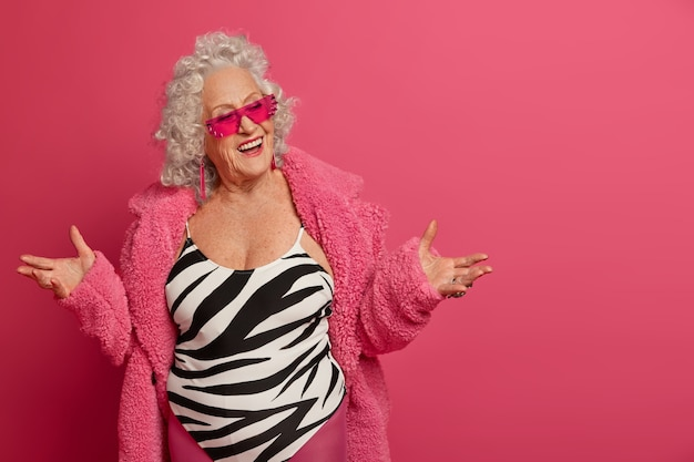 Pozytywna Modna Starsza Kobieta Rozkłada Dłonie Jest W Radosnym Nastroju Darmowe Zdjęcia