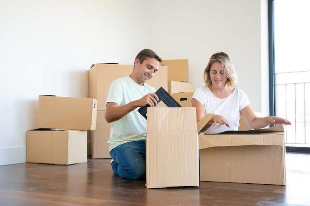 Pozytywna Para Rozpakowująca Rzeczy W Nowym Mieszkaniu, Siedząca Na Podłodze I Wyjmująca Przedmioty Z Otwartych Pudeł Darmowe Zdjęcia
