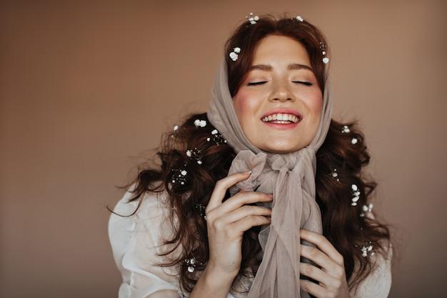 Pozytywna Rudowłosa Kobieta śmieje Się Z Zamkniętymi Oczami. Portret Kobiety W Beżowym Szaliku Z Białymi Kwiatami We Włosach. Darmowe Zdjęcia