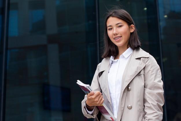 Pozytywna Szczęśliwa Młoda Azjatykcia Dziewczyna Uśmiechnięta I Patrzeje Prosto Przy Kamerą Outside Premium Zdjęcia
