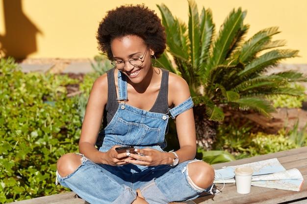 Pozytywna Turystka Używa Współczesnych Telefonów Komórkowych Do Wysyłania Wiadomości W Sieciach Społecznościowych, Trzyma Skrzyżowane Nogi, Nosi Okulary I Dżinsowe Ogrodniczki, Lubi Wakacje W Tropikach, Kawę I Mapę W Pobliżu Darmowe Zdjęcia