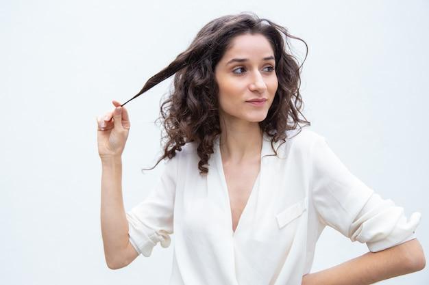 Pozytywna Ufna Piękna Kobieta Trzyma Pasemko Kędzierzawy Włosy Darmowe Zdjęcia