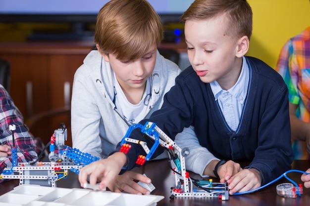 Pozytywne Dzieci Bawią Się I Montują Konstruktora W Pokoju Dziecięcym. Premium Zdjęcia