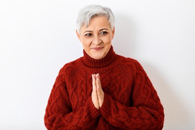 Pozytywne Emocje, Reakcja I Uczucia. Portret Atrakcyjnej Wesołej Starszej Pani Z Krótką Szarą Fryzurą, Która Wybuchnie śmiechem, Jest W Dobrym Nastroju, Trzymając Się Za Ręce W Namaste Darmowe Zdjęcia