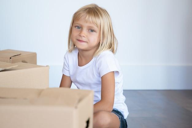 Pozytywne, Najsłodsze Jasne Włosy Dziewczynka Siedzi Na Podłodze W Pobliżu Pudełek Z Kreskówkami W Nowym Mieszkaniu I Patrzy Do środka Darmowe Zdjęcia