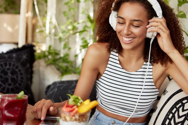 Pozytywnie Uśmiechnięta Młoda Kobieta Rasy Mieszanej Odpoczywa W Kawiarnianym Wnętrzu, Rozmawiając Ze Znajomymi W Sieciach Społecznościowych, Wyszukuje Ulubione Piosenki Na Liście Odtwarzania, Korzysta Z Aplikacji Mobilnej, Siada Na Wygodnej Sofie. Darmowe Zdjęcia