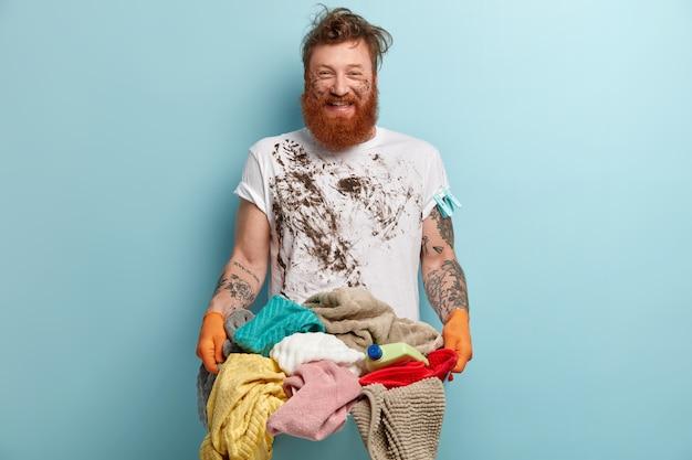 Pozytywnie Uśmiechnięty Brodacz Cieszy Się, że Prawie Kończy Prace Domowe, Ma Brudne Ubranie Darmowe Zdjęcia