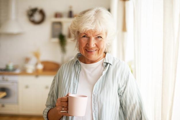 Pozytywnie Wyglądająca, Przyjaźnie Wyglądająca Starsza Starsza Kobieta O Siwych Włosach I Zmarszczkach Spędzająca Dzień W Domu, Popijając Rano Herbatę Lub Kawę Darmowe Zdjęcia