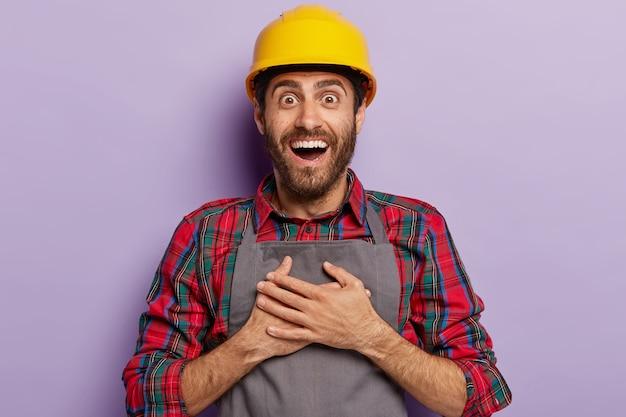 Pozytywnie Zadowolony Budowniczy, Pracuje W Firmie Budowlanej, Trzyma Ręce Na Piersi, Nosi żółty Kask Ochronny, Odzież Roboczą, Szeroko Się Uśmiecha Darmowe Zdjęcia