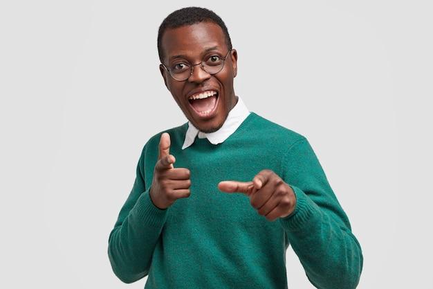 Pozytywnie Zadowolony Ciemnoskóry Mężczyzna Wskazuje Palcami Wskazującymi, Coś Wskazuje, Nosi Swobodny Zielony Sweter, Szeroko Się Uśmiecha Darmowe Zdjęcia