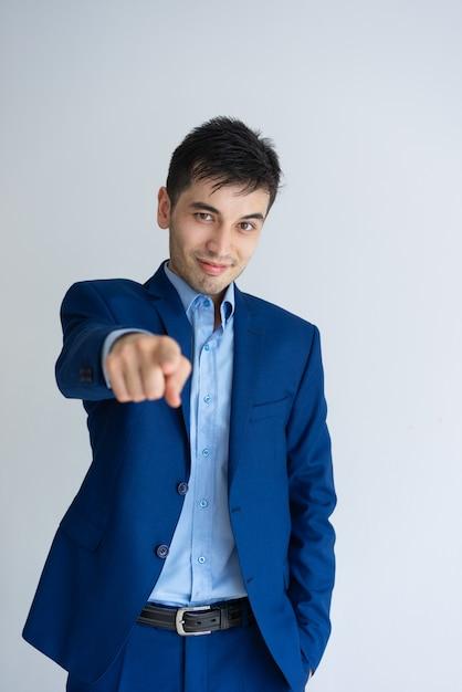 Pozytywny biznesowy mężczyzna wskazuje przy tobą i patrzeje kamerę Darmowe Zdjęcia