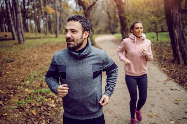 Pozytywny Kaukaski Brodaty Sportowiec Biegający W Przyrodzie Ze Swoją Dziewczyną. Premium Zdjęcia