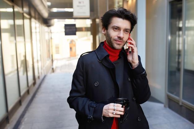 Pozytywny Młody Atrakcyjny Brązowowłosy Nieogolony Mężczyzna W Modnych Ubraniach Trzymający Kawę Na Wynos Podczas Wykonywania Połączenia Ze Swoim Smartfonem, Chodząc Po Tle Miasta Darmowe Zdjęcia