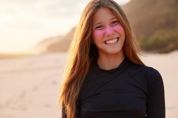 Pozytywny Młody, Doświadczony Surfer Uśmiecha Się Szeroko, Chroni Twarz Dwutlenkiem Cynku Darmowe Zdjęcia
