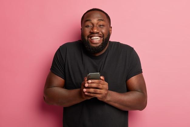 Pozytywny Pulchny Mężczyzna Z Gęstą Brodą, Dzieli Się świetnymi Wiadomościami W Sieciach Społecznościowych Z Przyjacielem, Będąc W Siódmym Niebie Od Szczęścia, Trzyma Nowoczesny Smartfon Darmowe Zdjęcia