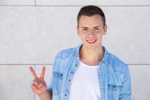 Pozytywny Rozochocony Studencki Facet Robi Pokoju Znakowi Darmowe Zdjęcia