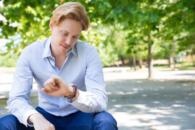 Pozytywny zadumany faceta czekanie na dziewczyny w parku Darmowe Zdjęcia