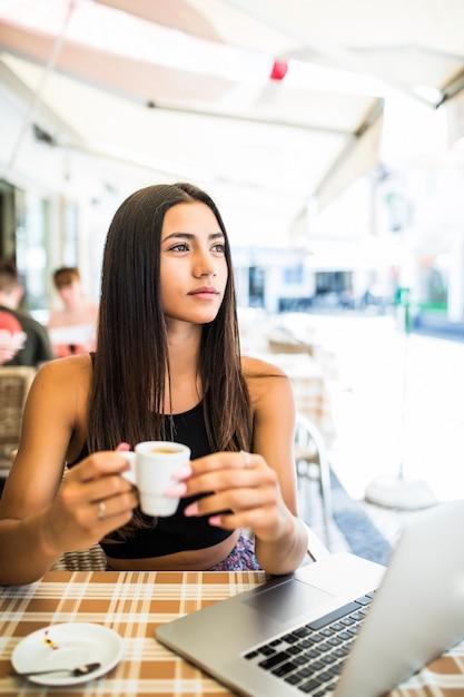 Praca Na Zewnątrz. Piękna Młoda Kobieta W Funky Kapelusz Działa Na Laptopie I Uśmiecha Się Siedząc Na Zewnątrz Darmowe Zdjęcia