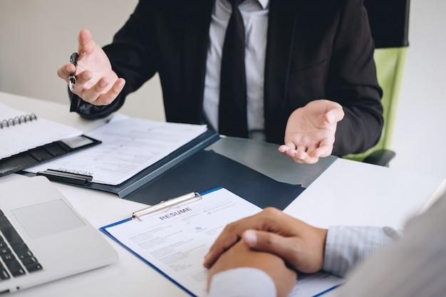 Pracodawca Lub Rekruter Czytający Cv Podczas Kolokwium O Swoim Profilu Kandydata, Pracodawca W Garniturze Prowadzi Rozmowę O Pracę, Zatrudnienie Zasobów Menedżera I Koncepcję Rekrutacji Premium Zdjęcia
