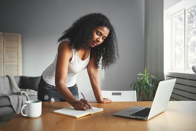 Pracowity Dzień Współczesnej Afrykańskiej Kobiety, Która Stoi Przy Drewnianym Biurku W Przytulnym Pokoju I Zapisuje Coś W Swoim Dzienniku, Z Skoncentrowanym Wyrazem Twarzy. Koncepcja Ludzi, Stylu życia I Technologii Darmowe Zdjęcia