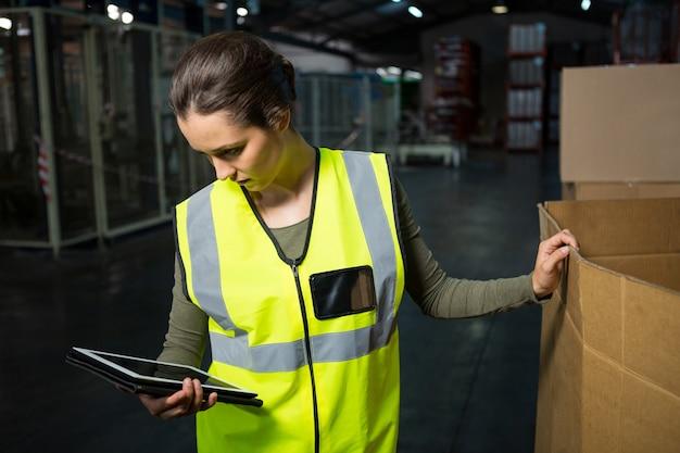 Pracownica Przy Użyciu Komputera Typu Tablet W Magazynie Darmowe Zdjęcia