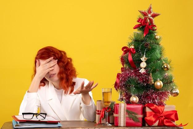 Pracownica Siedzi Za Stołem Z Prezentami świątecznymi I Drzewem Podkreślił Na żółto Darmowe Zdjęcia