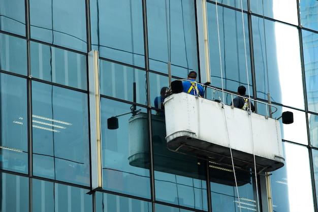 Pracownicy dźwigu kołyski czyste okna szklane wysokiego budynku Premium Zdjęcia