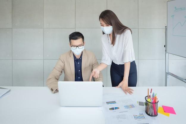 Pracownicy Firm Noszący Maski Podczas Pracy W Biurze, Aby Zachować Higienę, Przestrzegają Polityki Firmy. Zapobiegawczo W Okresie Epidemii Koronawirusa Lub Covid19. Premium Zdjęcia