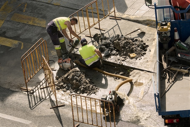 Pracownicy Naprawiający Zepsutą Fajkę Wodną Na Drodze Premium Zdjęcia