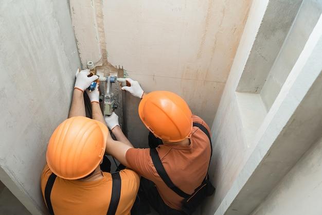 Pracownicy Przylutują Kran ścienny Do Wbudowanego Prysznica Premium Zdjęcia