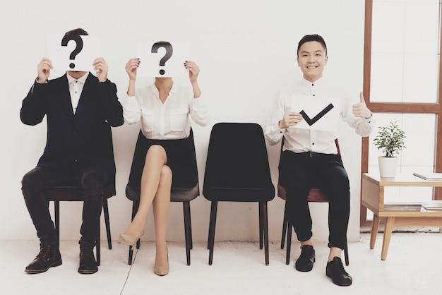 Pracownicy trzymają znaki różnych pytań Premium Zdjęcia